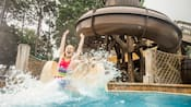 A girl slides into a pool with a large splash