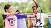 Two little girls take aim with bows and arrows as an instructor looks on