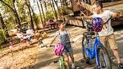 Deux enfants marchent à côté de leurs vélos devant une maison mobile stationnée alors que leurs parents les regardent assis sur des chaises pliantes