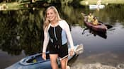 A woman holds an oar and walks out of a kayak at the side of a lake