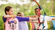 Two girls with bows and arrows take aim while an instructor looks on