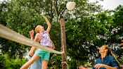 A man holds his daughter up to spike a volleyball over a net