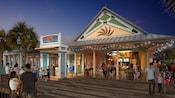 Des visiteurs fréquentent le Sebastians Bistro, un restaurant sur le thème des Caraïbes avec des palmiers devant.