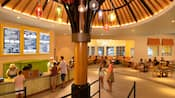 A food court with a large umbrella sculpture, hanging lights, a large menu displayed on the wall and Guests ordering at the front registers