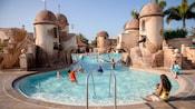 Uma mulher sentada com uma criança na borda de uma piscina com temática colonial espanhola observa outras pessoas jogarem