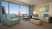 Una habitación de Huéspedes con un sofá, una mesa ratona, un cuadro de pared, 2lámparas, 2sillas y una ventana grande con vista al monorriel