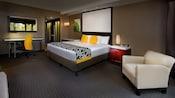 Una habitación de hotel con una cama grande, sillón y espacio de trabajo