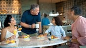 A family sits at a table enjoying fruit, muffins and drinks
