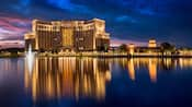 The sunsets over a grand hotel building and a large body of water