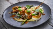 Four scallops drizzled with sauces served with hummus and a long, roasted carrot