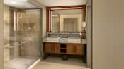 A bathroom with a walk in shower, double vanity and large mirror