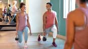 A man and woman smile while performing kettlebell lunges in fitness center