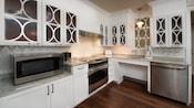 Une cuisine avec un micro-ondes, une cuisinière, un grille-pain et plusieurs armoires