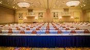 Várias mesas e cadeiras enfileiradas em um salão de festas