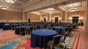 Mesas redondas cercadas por cadeiras em um salão de festas grande