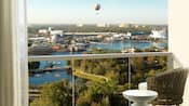 A hotel room balcony with a view of a passenger balloon hovering over Disney Springs across a lake