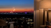 A hotel room window affords a view of fireworks exploding beyond a balcony at sunset