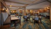 Um restaurante com mesas quadradas com booths e cadeiras