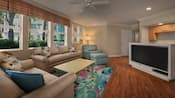 An open kitchen and living area with large view windows, a TV, upholstered chair and ottoman, sofa, love seat, coffee table and lamp