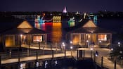 People stand on docks with 2 bungalows near a lake with a light parade of aquatic animals