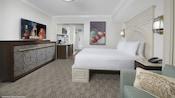 Una cómoda, TV, minicocina, cama, 2mesas laterales, 2 lámparas de pared y un sofá