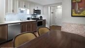 Una cocina con un lavavajillas tamaño estándar, hornalla y microondas junto a una mesa de comedor