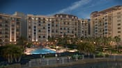 3 massive wings of Disney's Riviera Resort loom behind a large swimming pool lined with palm trees