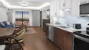 Le coin cuisine d'une suite d'hôtel avec un évier, une cuisinière, un lave-vaisselle et une table