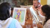 Un grupo de personas sentadas a la mesa pintan sus propias versiones de la torre de Rapunzel