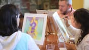 A group of people sitting at a table painting their own versions of Rapunzel's tower