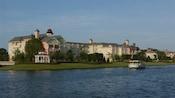 Um barco a vapor aberto navega ao lado do Disney's Saratoga Springs Resort and Spa, em estilo vitoriano