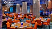 A modern restaurant with formally set tables, booths, decorative columns and abstract chandeliers that resemble underwater bubbles
