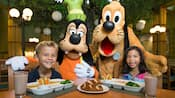 Goofy and Pluto pose for pictures with 2 young Guests enjoying a snack