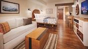 Un dormitorio y una sala de estar con un sofá, una mesa ratona, un cuadro de pared, una cama, una TV, cajones y una cocina pequeña