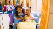 Une coiffeuse souriant avec une petite fille habillée en princesse dans un décor de salon