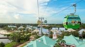 Disney Skyliner gondolas zip along a cable above Disney Resort hotel buildings
