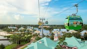 Disney Skyliner gondolas zip along a cable above Disney Resort hotel buildings
