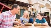 A family has lunch at an outside table in Harambe Market at Disney's Animal Kingdom Theme Park