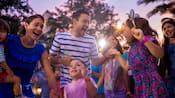 Several children and parents dancing together outside at sunset