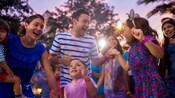 Varios niños y padres que bailan junto afuera en la puesta del sol