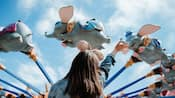 A girl waving up to the sky at the Dumbo the Flying Elephant attraction at Magic Kingdom park