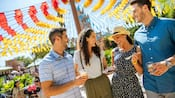 Two couples enjoy food and beverages at the Epcot International Food and Wine Festival
