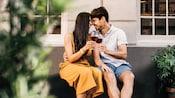 Una pareja joven sentada en un banco con copas de vino choca las narices