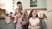 Un padre y sus 2 hijas preparan desayuno en la cocina de su villa en un hotel resort Disney