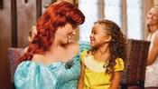La Princesa Ariel comparte una sonrisa con una joven Visitante sentada en su regazo