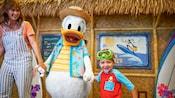 Donald Duck camina de la mano con una mujer y su hijo frente a un restaurante estilo cabaña