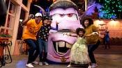 La mamá, el papá y sus 2 hijos adoptan una pose de dar miedo con el Vampiro Mater en Cars Land.