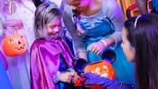 Alongside other costumed kids carrying pumpkins, a young girl wearing a cape and tiara trick or treats with 2 Disney Princesses