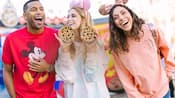 A delighted young woman holds up 2 chocolate chip cookies while 2 of her friends gleefully smile next to her