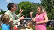 A Disney Cast Member engages in sign language with a female Guest, while her two children look on